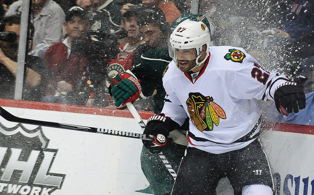 . Chicago defenseman Johnny Oduya mashes Minnesota left wing Jason Zucker into the boards during the first period.  (Pioneer Press: Ben Garvin)