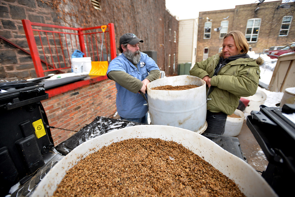 . Master brewer Dave Hoops, left and facilities manager Rob Strom heft barrells of spent beer brewing grain onto the back of Strom\'s truck at the loading dock outside Fitger\'s Brewhouse in Duluth on Wednesday December 12, 2012. The grain will feed a herd of six Scottish Highland steers which will be used to breed and provinde meat for Fitger\'s menu.  (Pioneer Press: Richard Marshall)