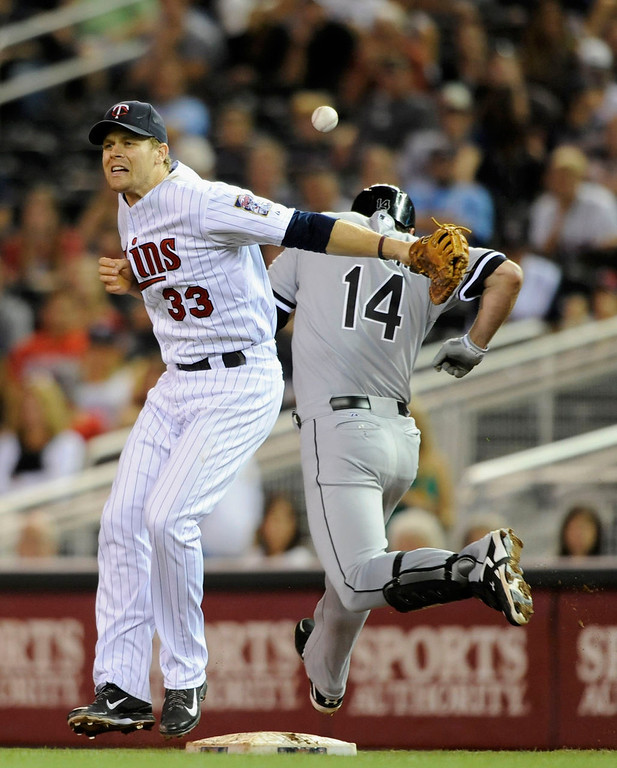 . Paul Konerko #14 of the Chicago White Sox is safe at first base as Justin Morneau #33 of the Minnesota Twins mishandles the throw from teammate Trevor Plouffe #24 during the eighth inning. (Photo by Hannah Foslien/Getty Images)