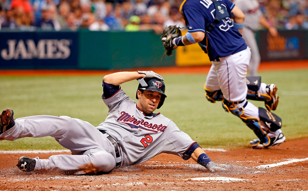 . Minnesota\'s Brian Dozier slides in for a run in the sixth inning as Rays catcher Jose Lobaton, right, turns to chase an errant throw. Dozier scored on a single by Jamey Carroll.  (Photo by J. Meric/Getty Images)