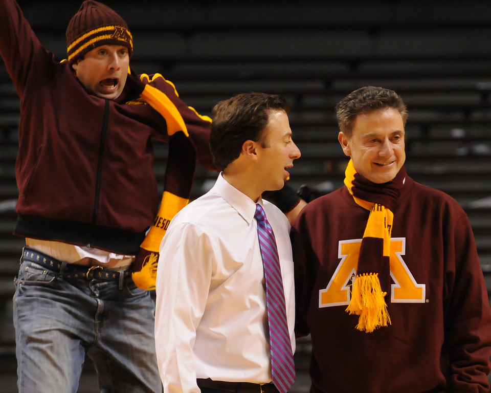 . Richard Pitino\'s older brother, Michael, tries to photobomb the Gophers coach and his dad, Rick Pitino, who came to watch Richard coach Minnesota against South Dakota State. (Pioneer Press: John Autey)