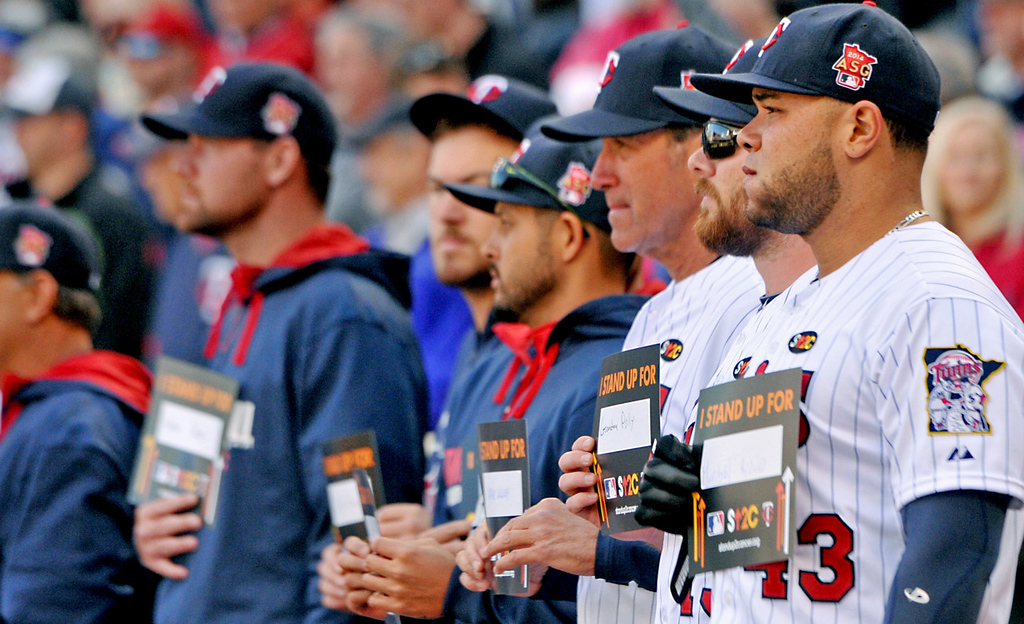 . Twins players hold up signs in support of general manager Terry Ryan and other cancer patients during a Cancer Awareness ceremony following the second inning. (Pioneer Press: John Autey)