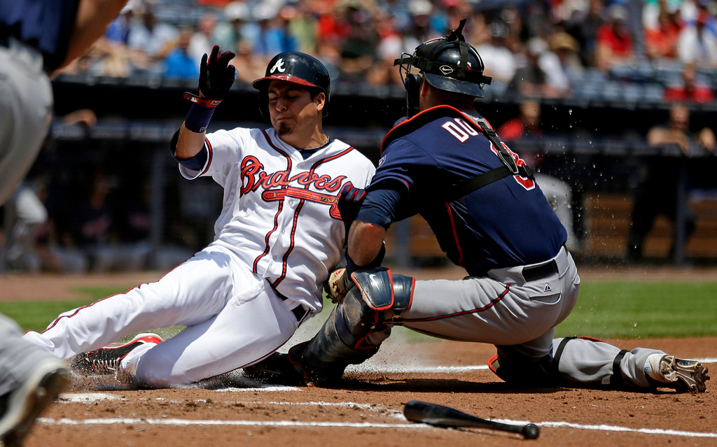 . Atlanta\' s Ramiro Pena, is tagged out at home plate by Twins catcher Ryan Doumit while attempting to score off a fly ball to left by Freddie Freeman in the first inning. (AP Photo/David Goldman)
