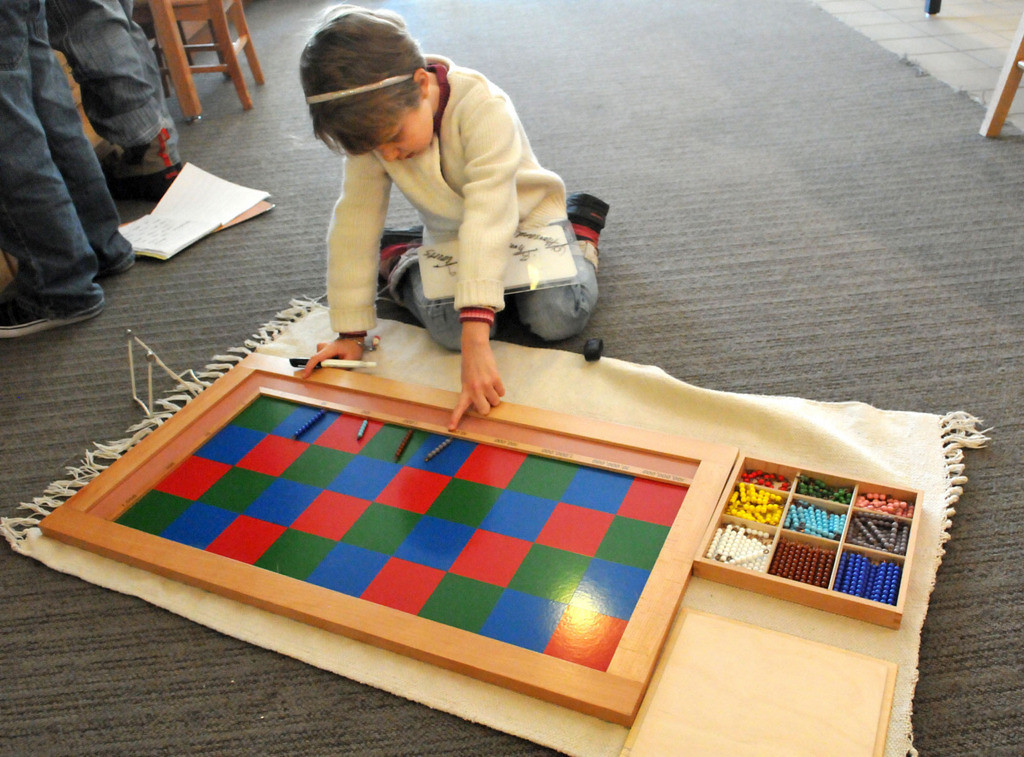 . Six-year-old Ella works on her math skills using the checkerboard system of learning long multiplication, a traditional Montessori system of learning. (Pioneer Press: John Doman)