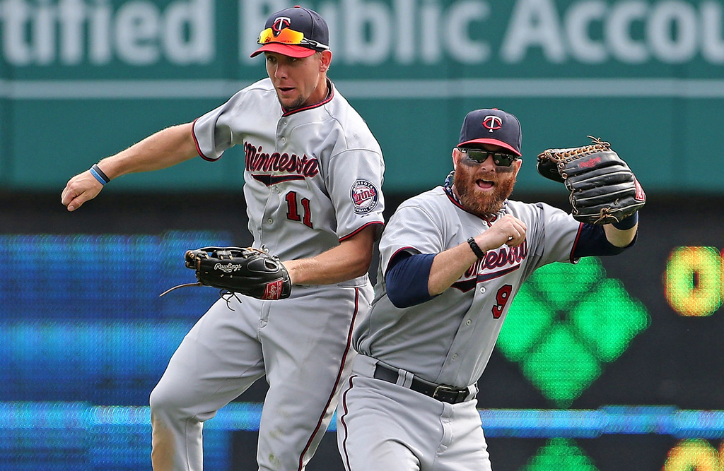 . Twins outfielders Clete Thomas, left, and Ryan Doumit celebrate their 7-6 win over the Detroit Tigers at Comerica Park in Detroit on Thursday, Aug. 22, 2013.  (Photo by Leon Halip/Getty Images)