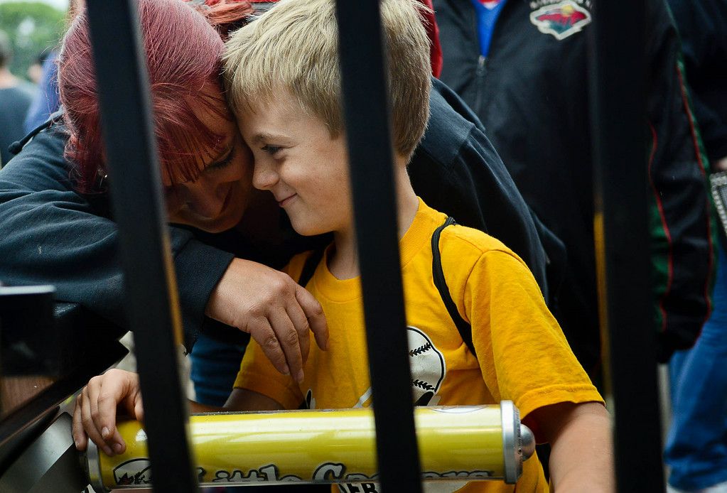 ". Tryphena Kimball and her son, Harley Carnes, 8, wait for the gates to open. ""I\'m excited to see them running around and hitting home runs and stuff,\"" said Harley, who was at Midway Stadium for this first Saints game. \""And I want to hear all the jokes.\"" (Pioneer Press: Ben Garvin)"