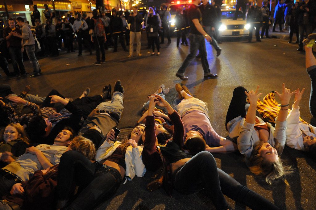 """. U of M fans take \""""selfies\"""" as they lie on the ground while Minneapolis police in riot gear, back, get into position to break up the crowd. (Pioneer Press: Sherri LaRose-Chiglo)"""