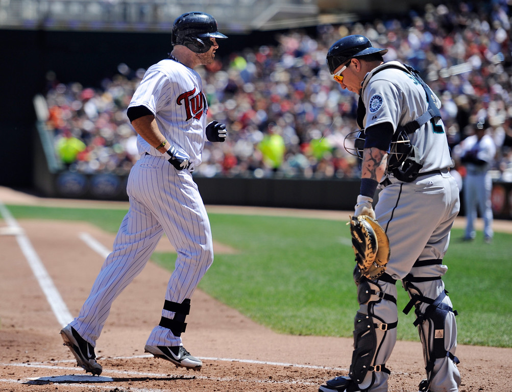 . Minnesota\'s Ryan Doumit, left, scores on a solo home run against Seattle Mariners starter Jeremy Bonderman, as catcher Jesus Sucre hangs his head during the second inning. (AP Photo/Craig Lassig)