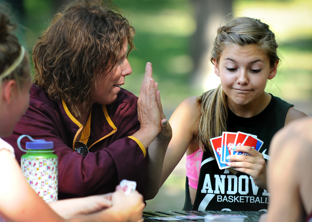 . Forest Lake girls cross country assistant coach Tracy Angelo, center, high-fives freshman Izzy Leininger, right, after she made a good play in Skip-Bo during a break in team practice at Minnehaha Falls Park in Minneapolis on Friday August 16, 2013. Leininger returned early from her run because of a hip problem, so Angelo taught her how to play Skip-Bo. (Pioneer Press: Jean Pieri)