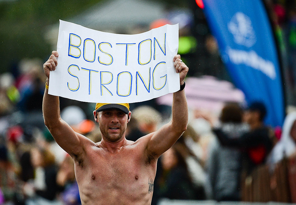 . Like Eichten, 33, of Minneapolis holds up a sign in tribute to the Boston Marathon as he crosses the finish line of the the Twin Cities Marathon (Pioneer Press: Ben Garvin)