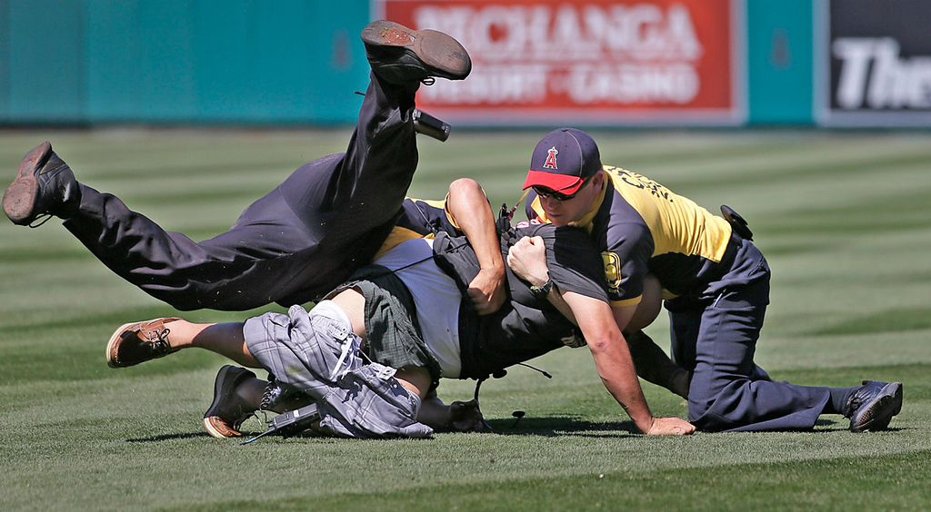 . Two security guards tackle a man who ran onto the field during the ninth inning of the game between the Angels and the Twins. (AP Photo/Jae C. Hong)