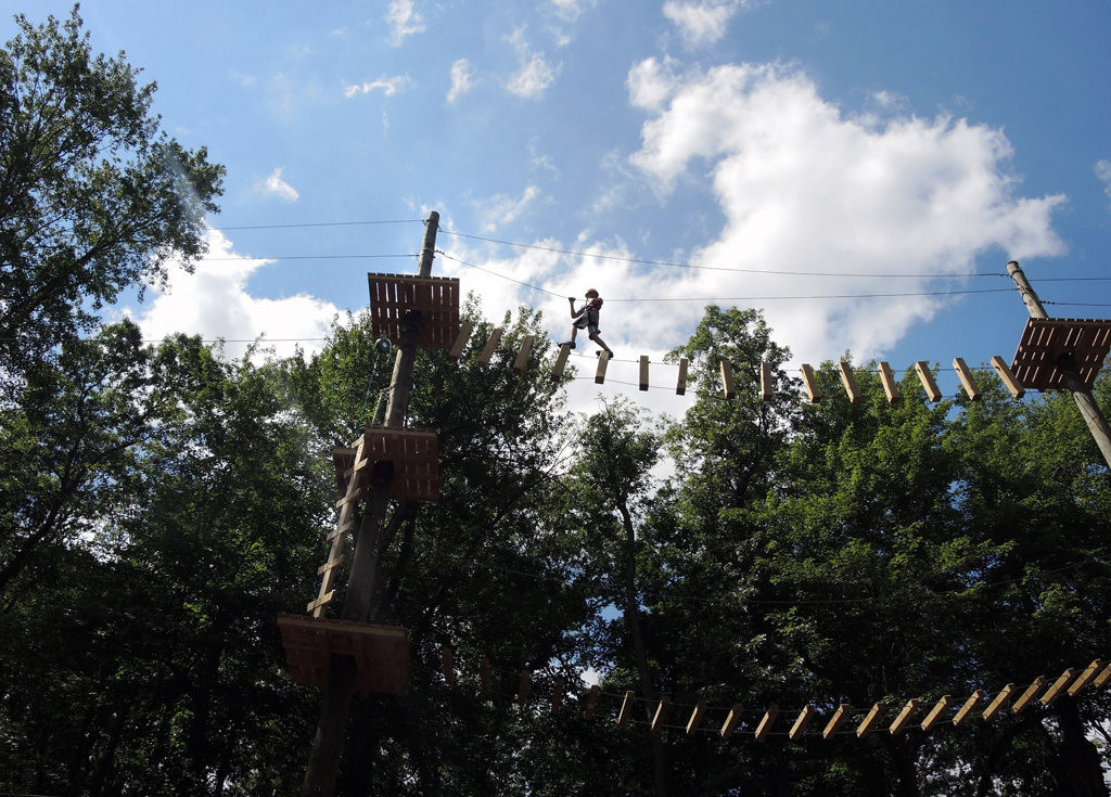 . A boy navigates his way across a bridge made of individual wooden pegs in the most difficult section of the challenge course at the Aerial Adventure Park at Trollhaugen on Saturday, August 17, 2013.   (Pioneer Press: Chris Polydoroff)