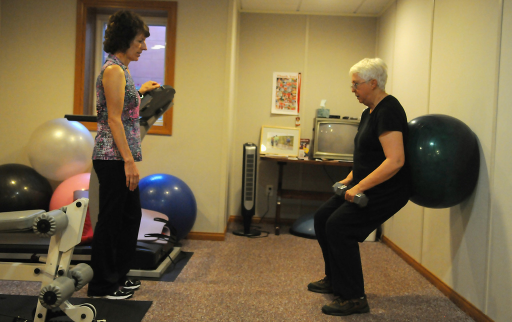 . Annie Elmer, left, coaches Toni Lambert of St. Paul Park as Lambert uses an exercise ball for therapy for her back and core muscles at Elmer\'s Cottage Grove home. (Pioneer Press: John Autey)