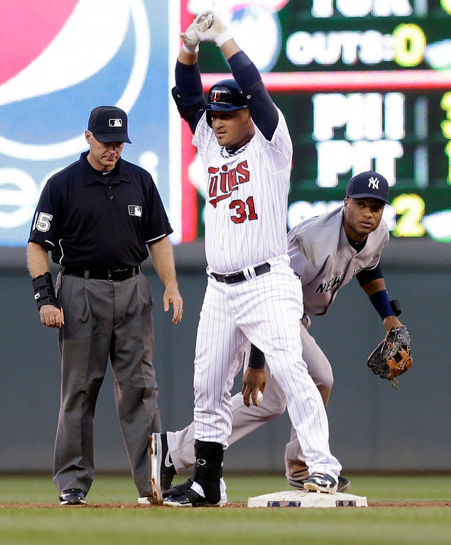 . Yankees second baseman Robinson Cano, right, circles around Minnesota Twins\' Oswaldo Arcia after Arcia beat the tag in the fourth inning. The second base umpire is Ed Hickox. (AP Photo/Jim Mone)