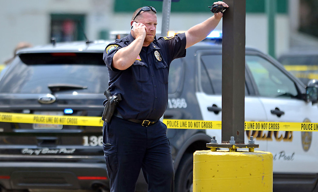 . A law enforcement officer speaks on the phone near the intersection of Smith Avenue and Dodd Road in West St. Paul, where Mendota Heights Police Officer Scott Patrick was shot and killed during a traffic stop on Wednesday. (Pioneer Press: Ben Garvin)