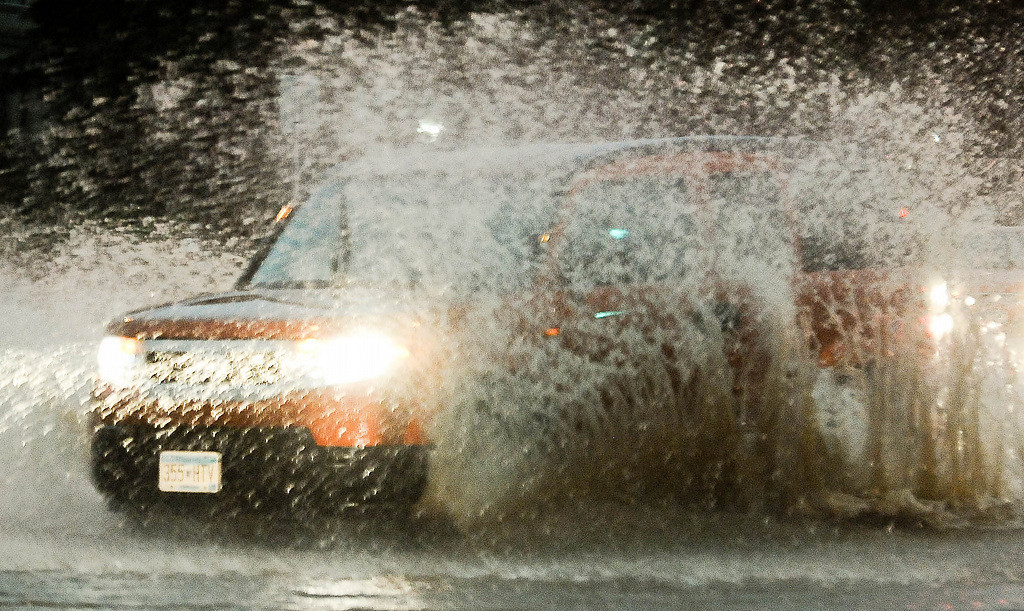 . A car plows through deep water on the corner of Stinson and N.E. Broadway in Minneapolis. (Pioneer Press: Ben Garvin)