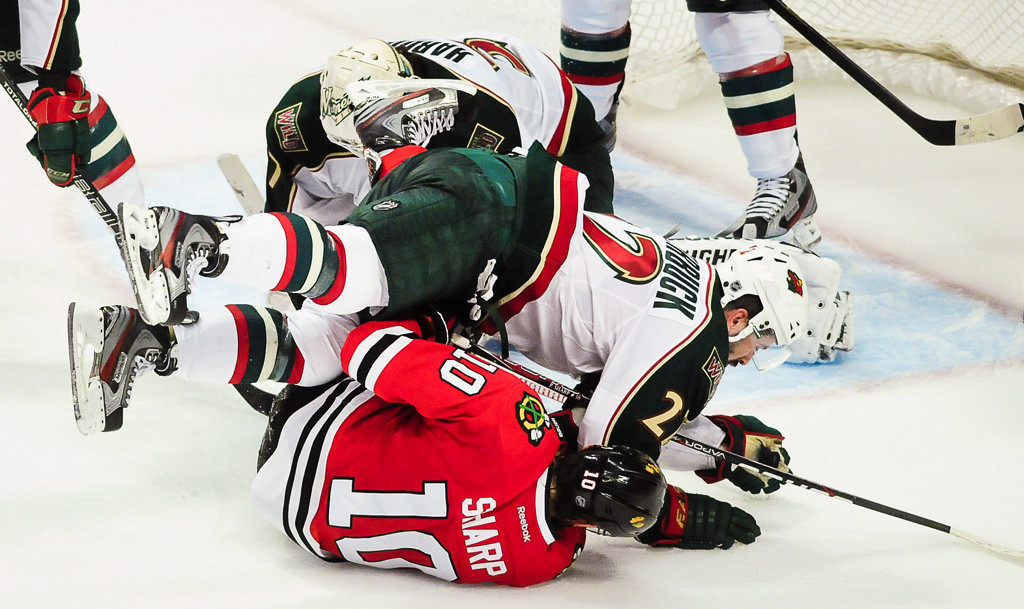 . Minnesota Wild right wing Cal Clutterbuck can\'t stop in time and falls over the top of Chicago Blackhawks center Patrick Sharp in overtime. (Pioneer Press: Ben Garvin)