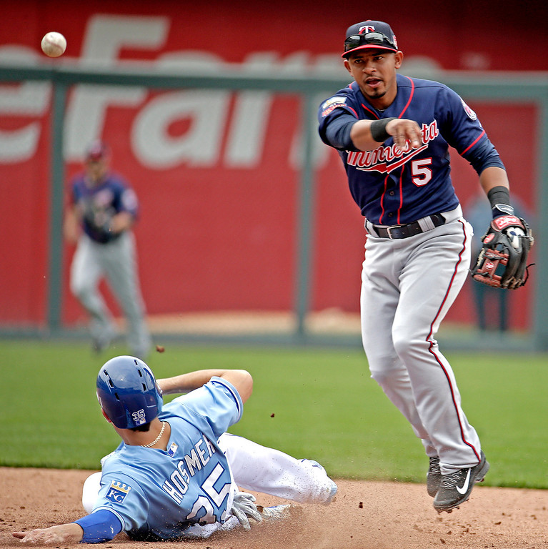 . Minnesota Twins shortstop Eduardo Escobar (5) throws to first for the double play after forcing Eric Hosmer (35) out at second during the fifth inning. (AP Photo/Charlie Riedel)