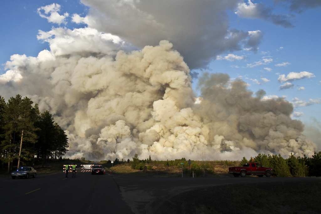 . A smoke plume rises high above a road block at the intersection of County A and Ross Road east of Solon Springs, Wis. (Duluth News-Tribune: Clint Austin)