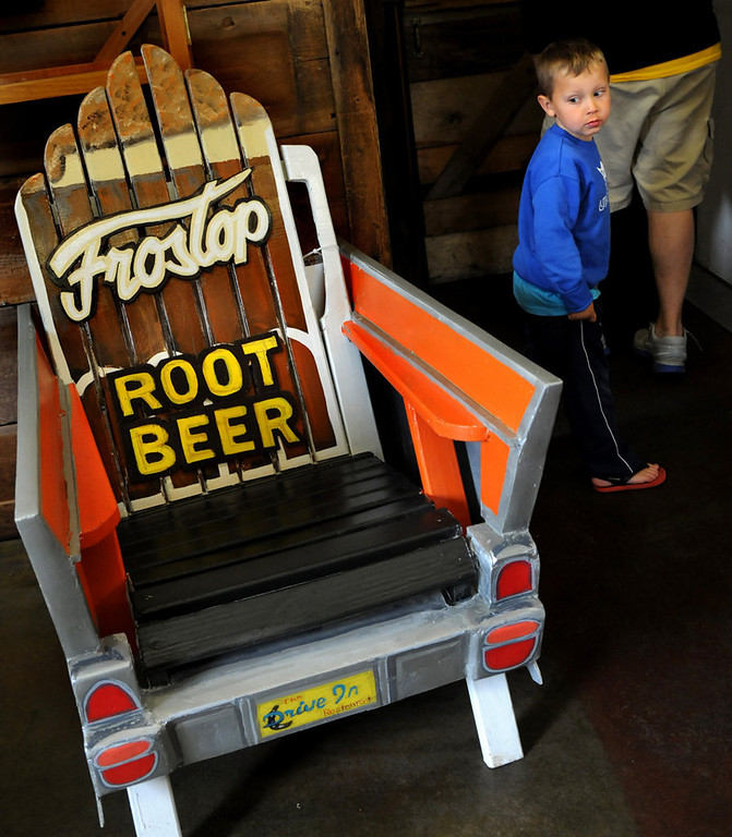 """. Preston Eichmeier, 4, of Altoona, Iowa, eyes a chair titled \"""" \'57 Chevy\"""" by Derek Lusche in Taylors Falls Friday July 26, 2013. The chair is part of the Highway 8 Chairs project in Chisago County that has 37 Adirondack chairs, each painted by an area artist, along the stretch of highway between Chisago City and Taylors Falls. The project was launched by the Chisago Lakes Area Community Foundation, a local nonprofit group, to bring visitors back to businesses who have suffered during recent road work. (Pioneer Press: Jean Pieri)"""
