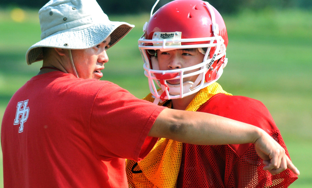 ". Highland Park assistant coach Elliott Vang gives instructions to sophomore defensive back Jer Ger Xiong during practice. ""Race doesn�t matter to me, but it is nice to know that there is another of my kind on the coaching staff,\"" said Xiong.  (Pioneer Press: John Doman)"