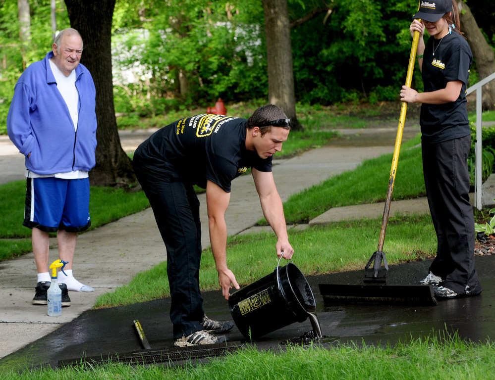 . Bob Kuehn watches as the Jet-Black crew reseals his driveway.  (Pioneer Press: Jean Pieri)