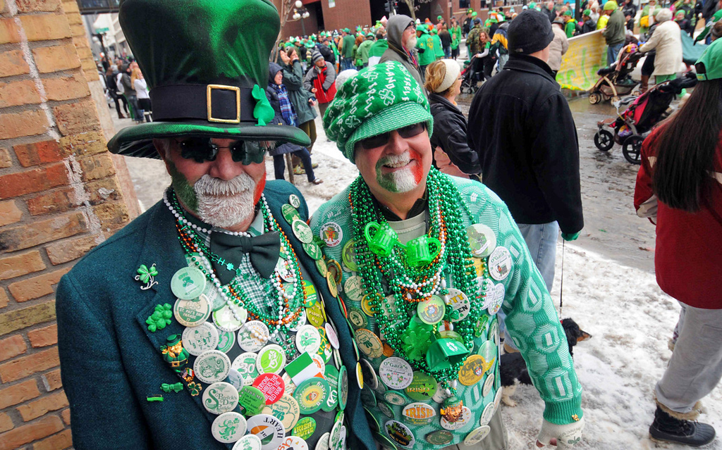 . Covered with 48 years of parade commemorative buttons, Michael O\'Dilley, left, and Mark Wilson enjoy the annual St. Patrick\'s Day parade.  (Pioneer Press: Scott Takushi)
