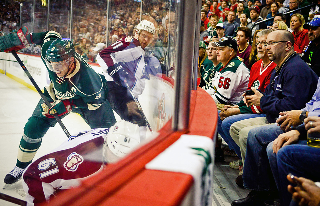 . Minnesota\'s Mikko Koivu goes after the puck while pursued by Colorado\'s Jamie McGinn as fans watch in the second period.  (Pioneer Press: Ben Garvin)
