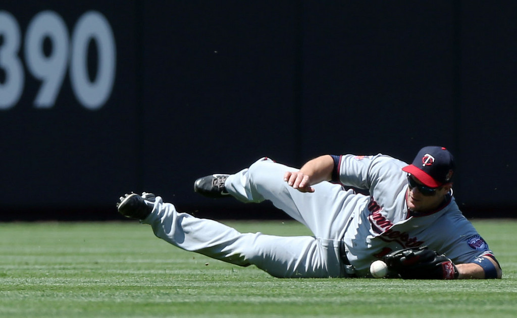 . Minnesota Twins left fielder Josh Willingham dives but misses a ball that went for a double  by Colorado Rockies\' Nolan Arenado in the first inning. (AP Photo/David Zalubowski)