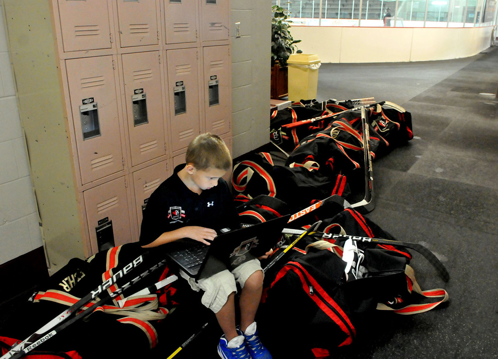 . Third-grader Mason Johnson from Lakeville does some work on his laptop atop some hockey equipment bags in between academic classes and hockey ice time at Northern Educate Hockey Academy at Eagan Ice Arena. The K-12 school, with three hours of ice time each day, is a program on the cusp of a massive expansion.   (Pioneer Press: John Doman)