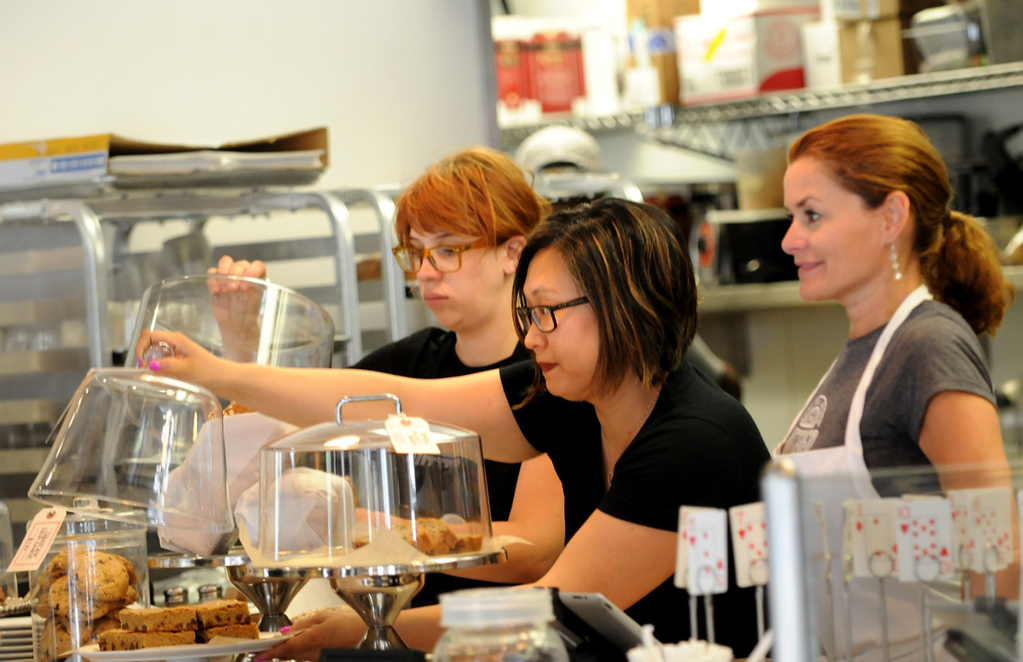 . Jennifer Lueck, center, co-owner of the Buttered Tin, secures a glass cover over fresh-baked goods at the cafe. (Pioneer Press: Jean Pieri)
