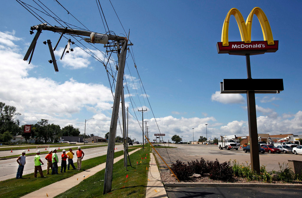 . A team of WE Energy workers assess damage to utility lines near the McDonald\'s and Northland Mall in Appleton, Wis. (AP Photo/The Post-Crescent, Sharon Cekada)