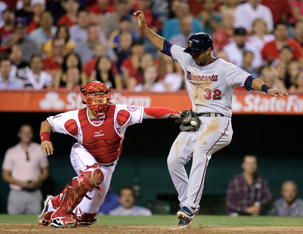 . Los Angeles Angels catcher Hank Conger, left, tags out Minnesota Twins\' Aaron Hicks during the fourth inning of a baseball game on Monday, July 22, 2013, in Anaheim, Calif. (AP Photo/Jae C. Hong)