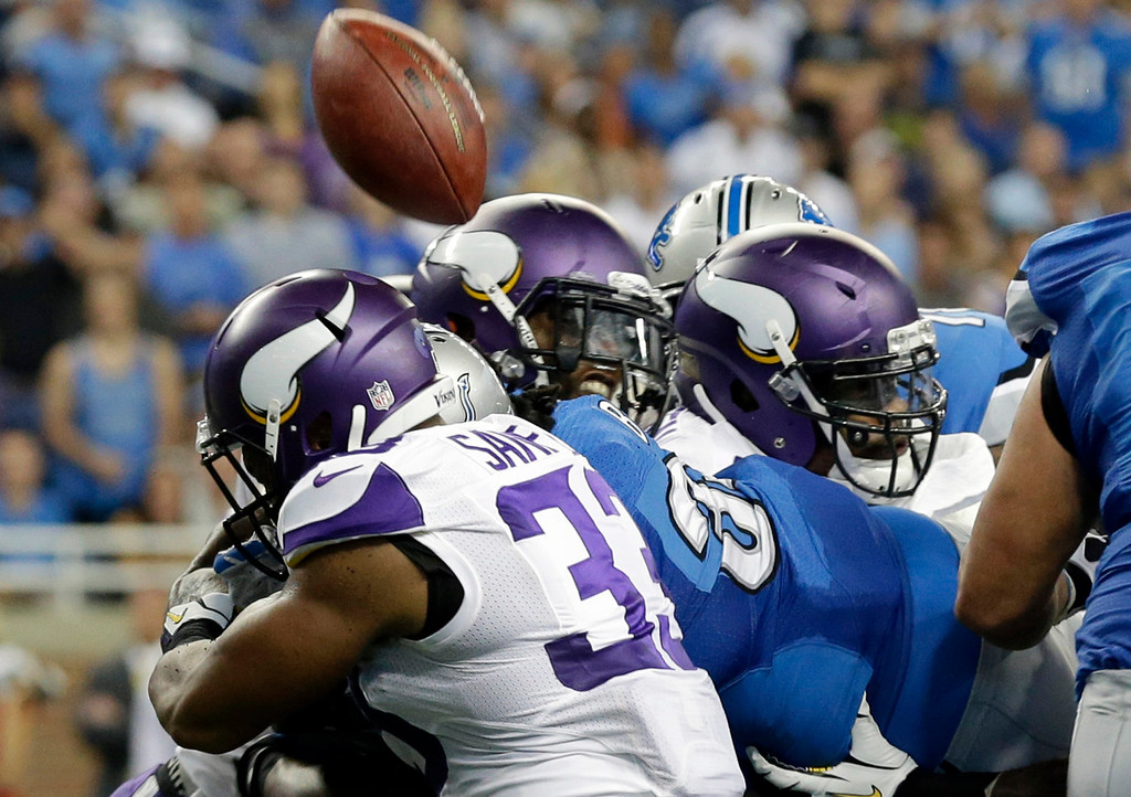 . Lions running back Joique Bell, center in blue, loses control of the ball after crossing the goal line during the second quarter against the Vikings. After review, it was determined that the ball crossed the plane of the goal line before Bell lost it.  (AP Photo/Paul Sancya)