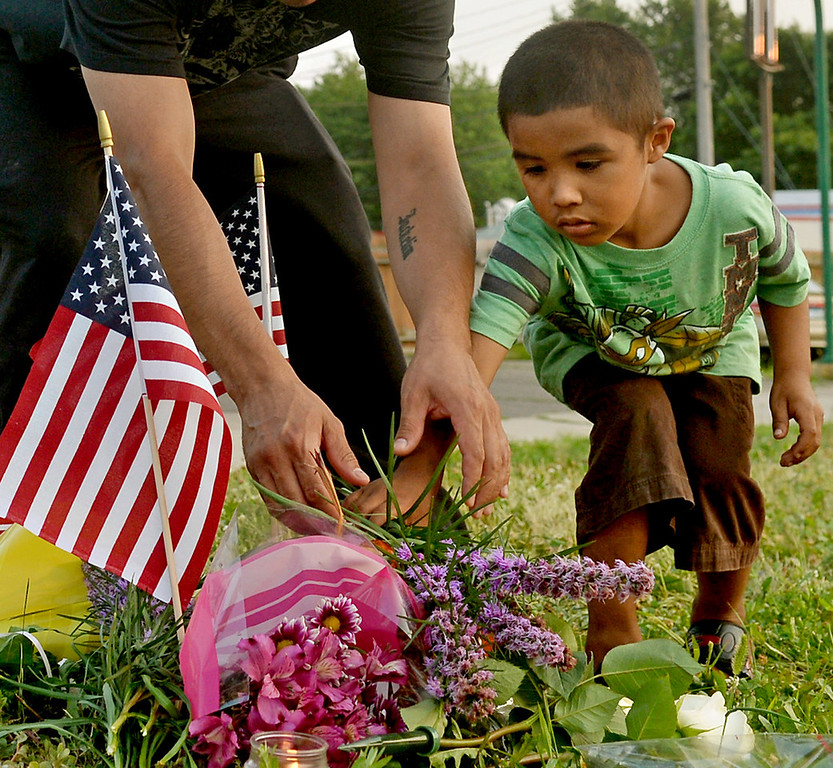 . Five-year-old Jose De Jesus Maritnez Jr. adds flowers to a memorial with his father, Jose De Jesus Martinez, Sr., before a candlelight vigil in honor of slain Mendota Heights Police Officer Scott Patrick. (Pioneer Press: John Autey)