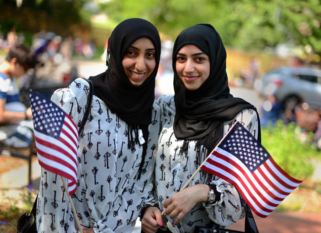 . Fatimah Al Khunaizi, left, and her cousin, Khatoon Al Ghanim, hold American flags along the Como Avenue parade route. The women are from Qatif, Saudi Arabia, and are studying at the University of Minnesota. (Pioneer Press: Chris Polydoroff)