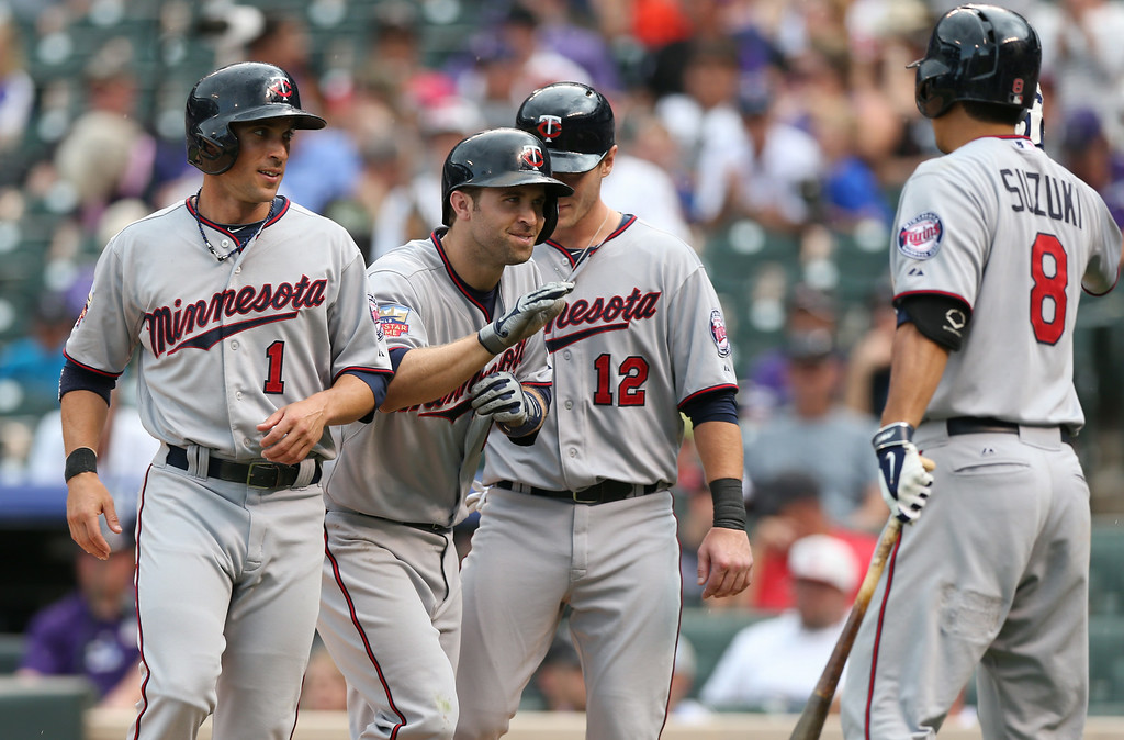 . Minnesota Twins\' Brian Dozier, second from left, is congratulated by teammates, from left, Sam Fuld, Chris Hermann and Kurt Suzuki after Dozier hit a three-run home run against the Colorado Rockies in the ninth inning. (AP Photo/David Zalubowski)