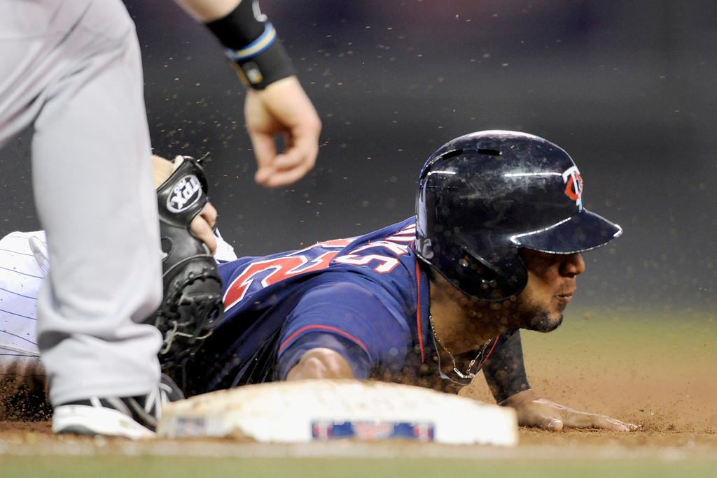 . Aaron Hicks of the Minnesota Twins dives back to first base safely as Mike Carp of the Boston Red Sox applies a tag during the fifth inning. (Photo by Hannah Foslien/Getty Images)