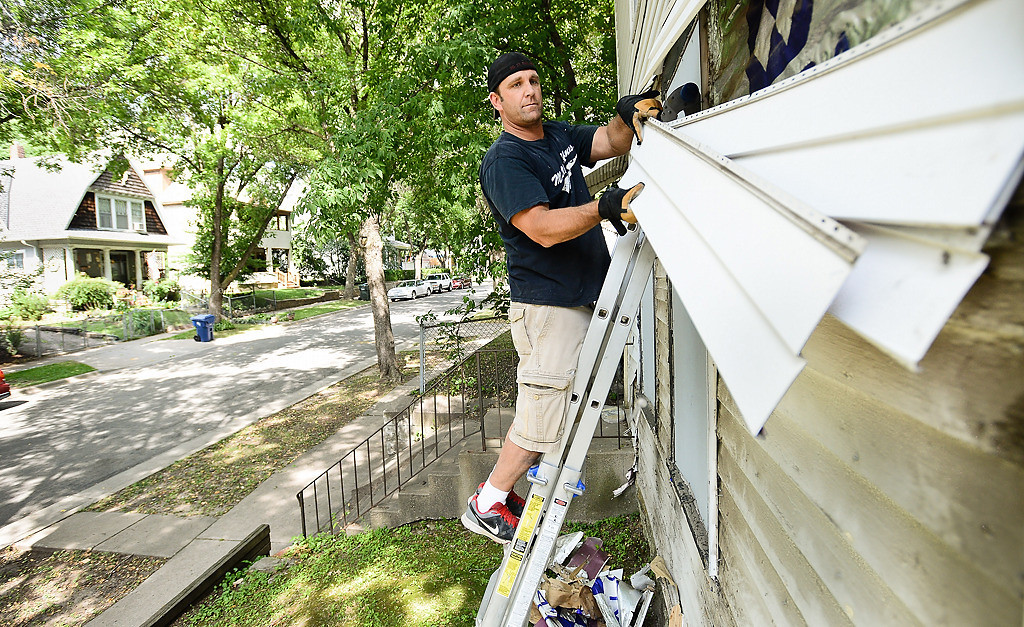 . Construction worker Tom Bosworth removes metal siding at a boarded up former crack house across 4th Street from Jim and Holly Wardlaw\'s house. (Pioneer Press: Ben Garvin)