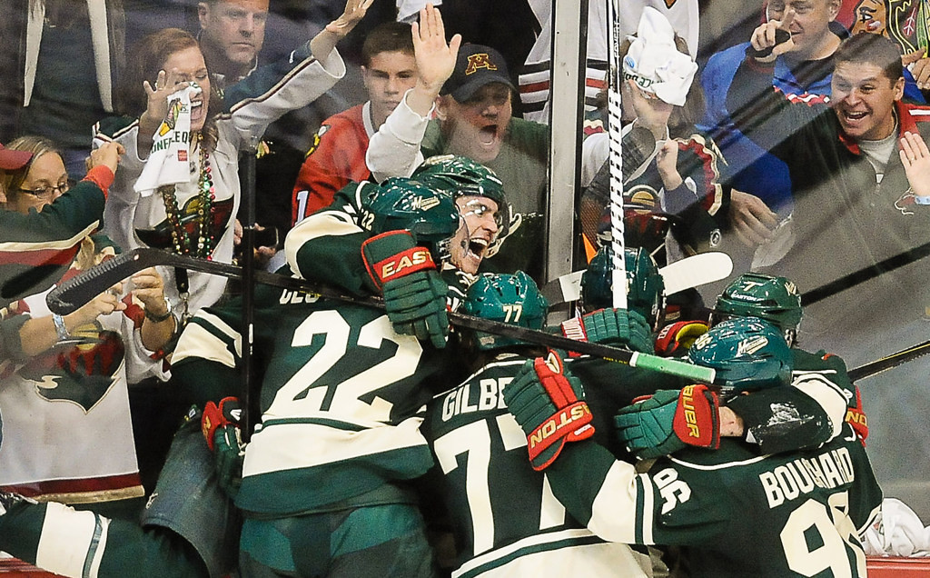 . Minnesot\'s Zach Parise, facing, and other Wild players swarm Jason Zucker after he scored the winning overtime goal against the Blackhawks.  (Pioneer Press: Ben Garvin)