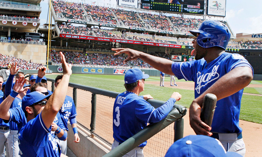 . Kansas City\'s Lorenzo Cain, right, hams it up as he returns to his dugout after scoring on a hit by Justin Maxwell off  Twins starter Scott Diamond in the second inning.  (AP Photo/Andy Clayton-King)