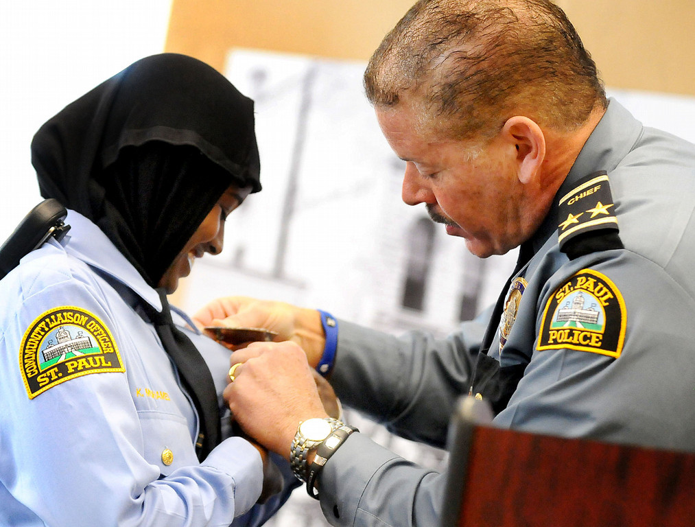 . St. Paul Community Officer Kadra Mohamed smiles  as she receives her badge from St. Paul Police Chief Thomas Smith, right, on Saturday. The police department introduced the hijab headscarf during the ceremony and Mohamed is the first officer in Minnesota to wear one.(Pioneer Press: Sherri LaRose-Chiglo)