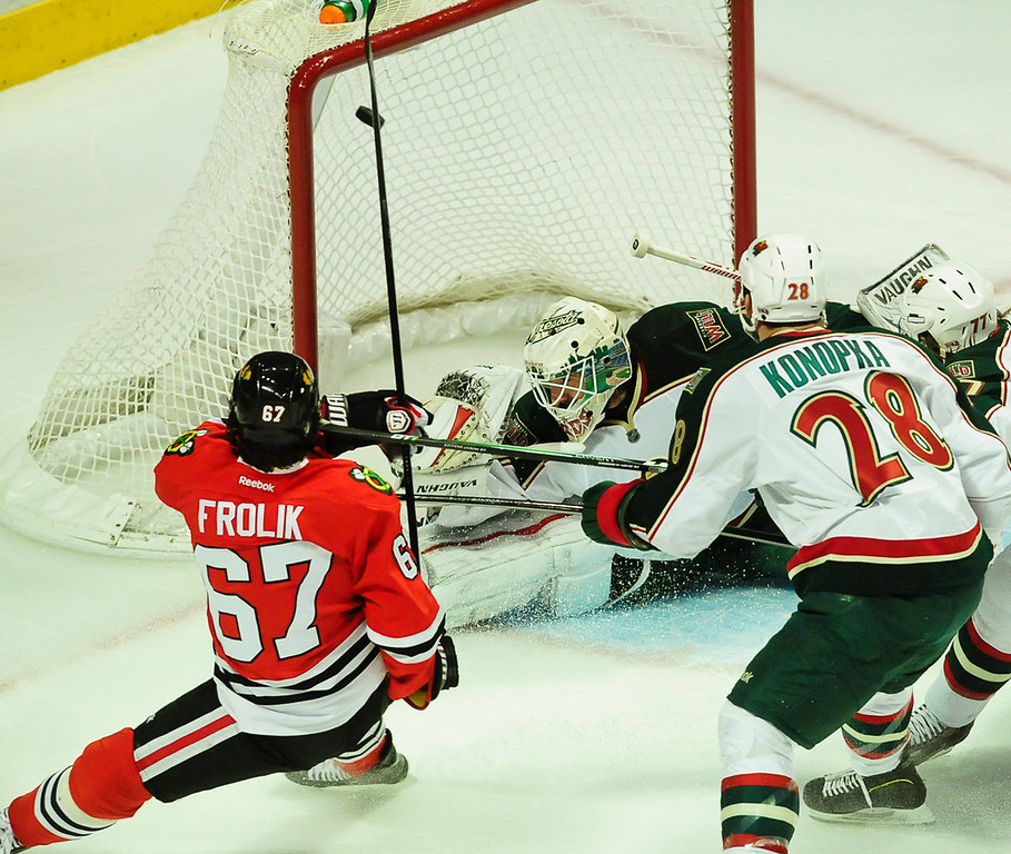 . Chicago Blackhawks center Michael Frolik scores the game\'s first goal past Minnesota Wild goalie Josh Harding in the first period. At right is Minnesota Wild center Zenon Konopka. (Pioneer Press: Ben Garvin)