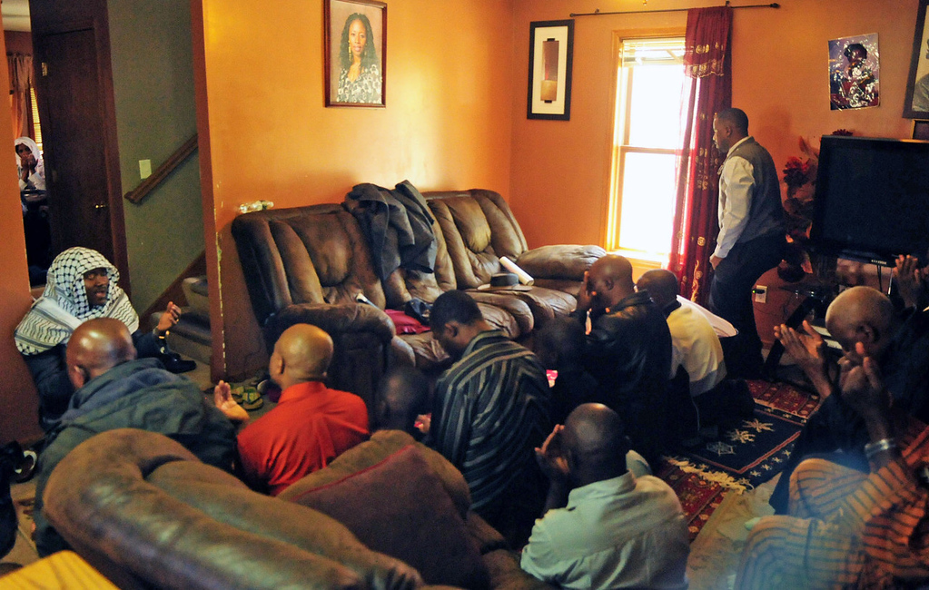 . Imam Mohamed Dukuly, top left, leads prayers on Thursday for the men in the home of Lancine Fofana and Madousu Kanneh, the father and mother of Zack Mohamed Fofana, age 10, who was killed while on a field trip with his class to Lilydale Regional Park.  (Pioneer Press: Scott Takushi)