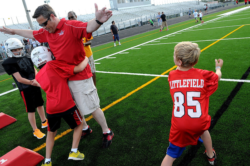. Centennial Youth Football Association player safety coach Sean Gothier gives Nick Popp some hands-on instructions in proper tackling form. (Pioneer Press: Sherri LaRose-Chiglo)