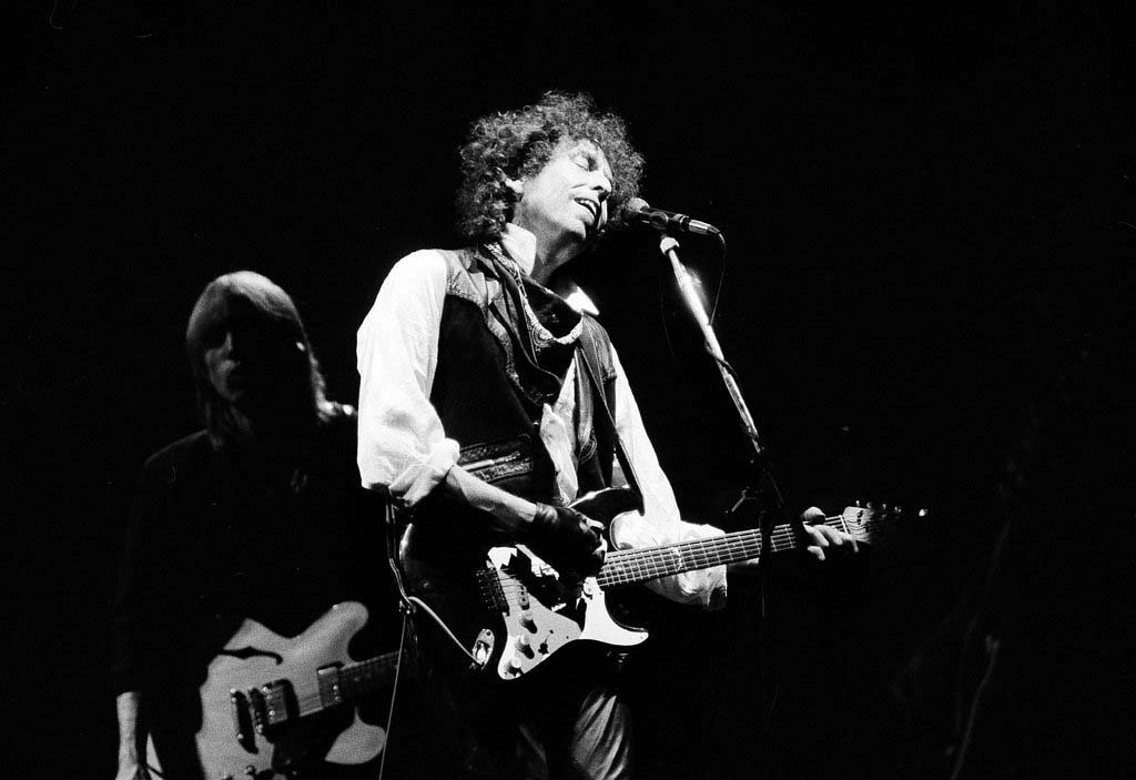 """. Singer/songwriter Bob Dylan opens his \""""True Confessions\"""" tour in the San Diego Sports Arena to a sold-out house of about 17,000, June 9, 1986.  It is Dylan\'s first U.S. tour since 1981.  Also appearing with Dylan is Tom Petty and the Heartbreakers.  (AP Photo/Howard Lipin)"""