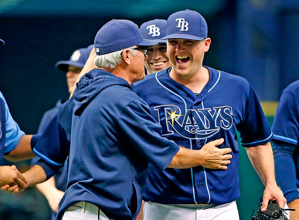 . Rays manager Joe Maddon congratulates pitcher Jake McGee, who threw a scoreless ninth to get the save in Tampa\'s 4-3 win over the Twins.  (Photo by J. Meric/Getty Images)