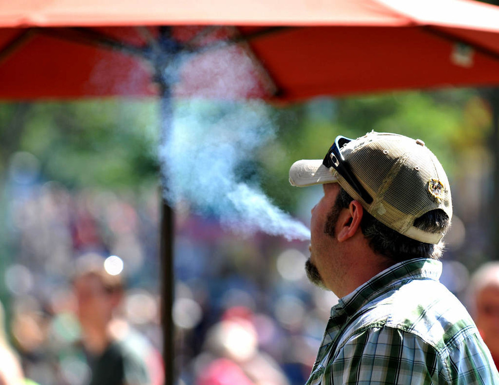 . Ed Jaxton of Minneapolis enjoys a cigarette at a designated smoking area near the Grandstand. (Pioneer Press: John Doman)