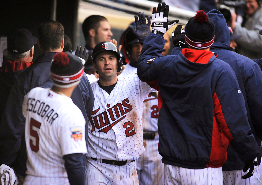 . Minnesota Twins  Brian Dozier, center, celebrates in the Twins dugout after scoring the go-ahead run on a throwing error by Kansas City Royals pitcher Wade Davis during the ninth inning of a baseball game in Minneapolis, Sunday, April 13, 2014. Minnesota won 4-3. (AP Photo/Tom Olmscheid)