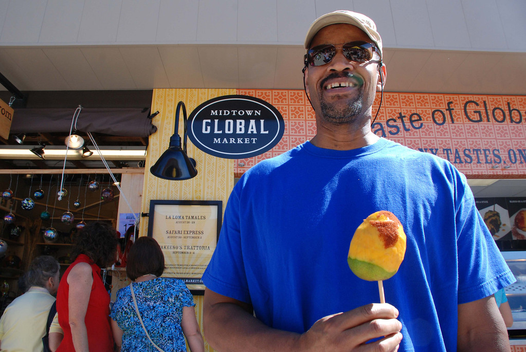 . A man poses with a mango on-a-stick in the International Bazaar during the 2010 Minnesota State Fair. Photo courtesy of the Minnesota State Fair.